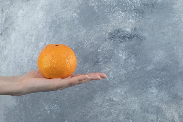Main féminine tenant une seule orange sur une table en marbre.