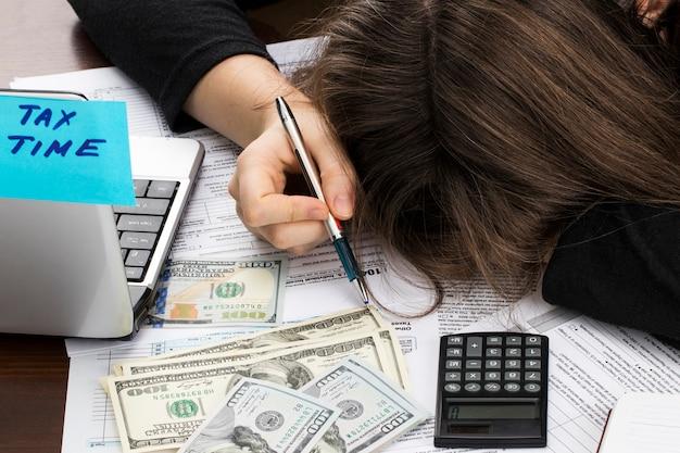 Main féminine tenant un stylo et à l'aide de la calculatrice tout en remplissant la déclaration de revenus des particuliers, gros plan