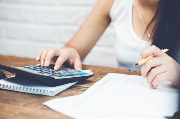 Main féminine tenant un stylo et à l'aide de la calculatrice