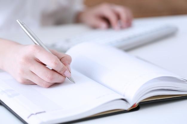 Main féminine tenant un stylo argenté prêt à prendre note