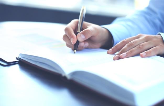 Main féminine tenant un stylo prêt à prendre note dans une feuille de cahier ouverte.