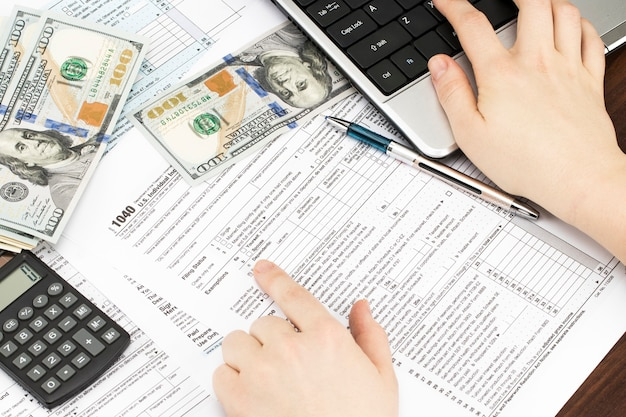 Main féminine tenant un stylo et utilisant une calculatrice tout en remplissant la déclaration de revenus individuelle, gros plan.