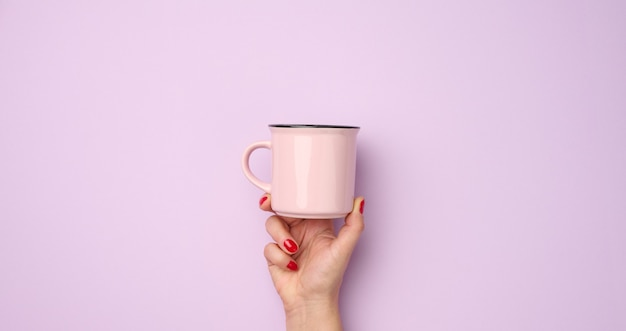 Main féminine tenant une tasse en céramique rose sur fond violet, temps de pause et boire du café, bannière