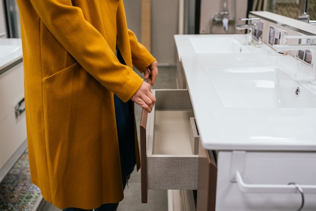 Main féminine tenant un tiroir blanc sur un magasin
