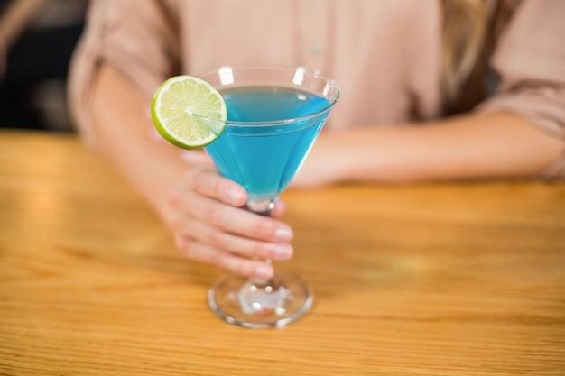 Main féminine tenant un verre à cocktail
