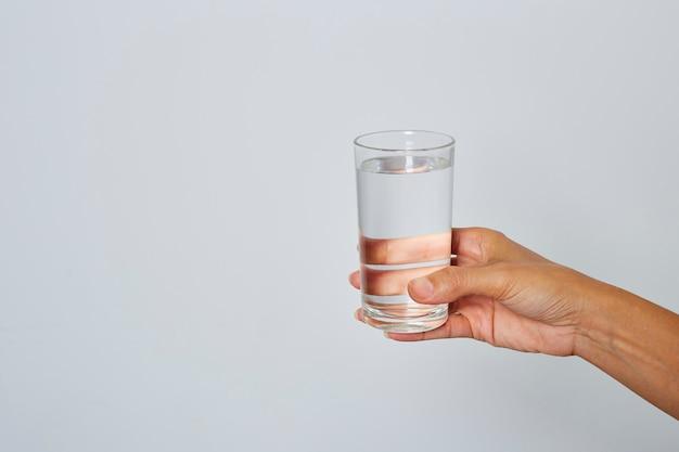 Main féminine tenant un verre d'eau
