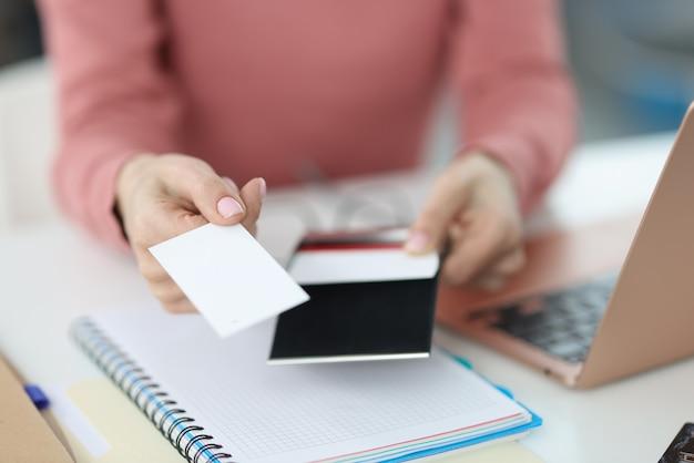 Main féminine tend une carte de visite sur le lieu de travail. impression et création de concept de cartes de visite