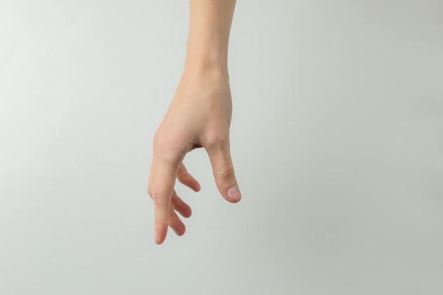 La main féminine tend la main pour prendre sur un fond blanc.