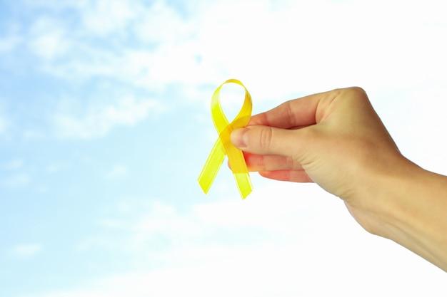 Main féminine tenir le ruban de sensibilisation au cancer infantile sur fond de ciel