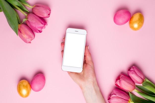 Main féminine tenir le téléphone sur une surface rose avec des fleurs et des oeufs de pâques