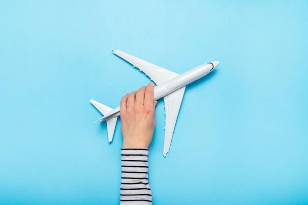 Main féminine tient un avion sur un bleu. vol concept, billets, réservation, recherche de vol, voyage.