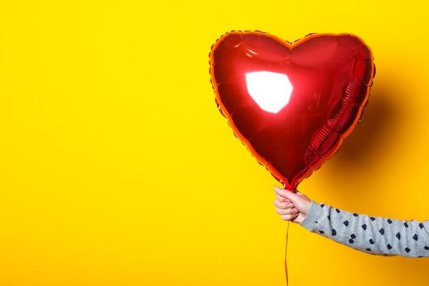 La main féminine tient un ballon gonflable en forme de coeur sur un fond jaune.
