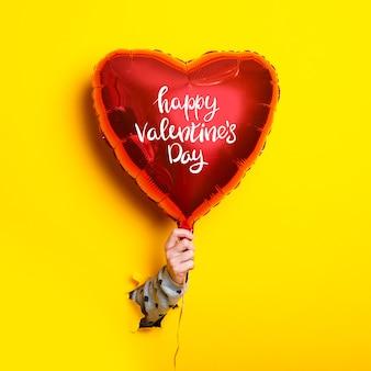 La main féminine tient un ballon gonflable avec l'inscription happy valentines day sur un fond jaune déchiré.