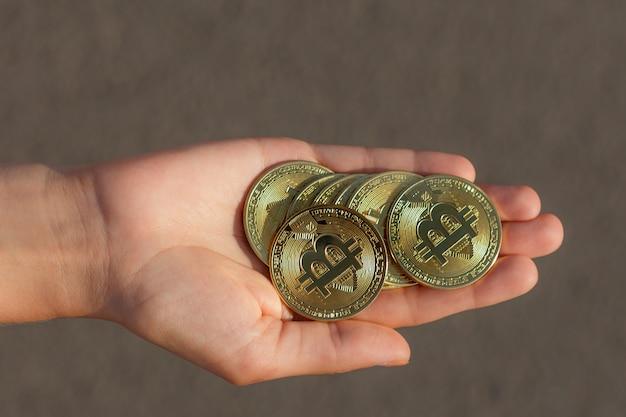 La main féminine tient beaucoup de grosses pièces de monnaie bitcoin en crypto-monnaie d'or sur le sol gris au coucher du soleil.
