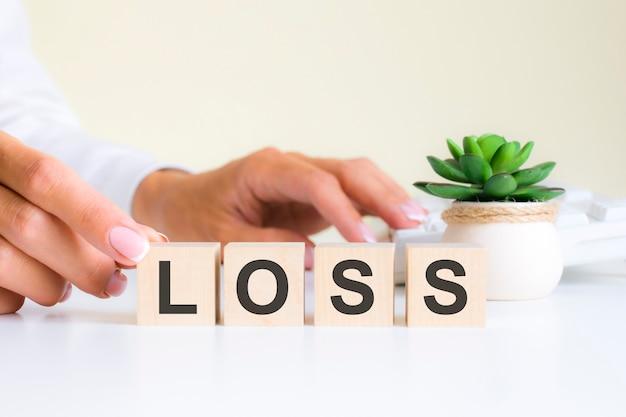 La main féminine tient un bloc avec la lettre l du mot perte. le mot est situé sur une table de bureau blanche sur le fond d'un clavier blanc. concepts financiers, marketing et commerciaux