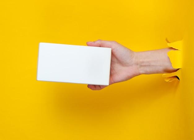 Une main féminine tient une boîte blanche à travers du papier jaune déchiré. concept de mode créative minimaliste