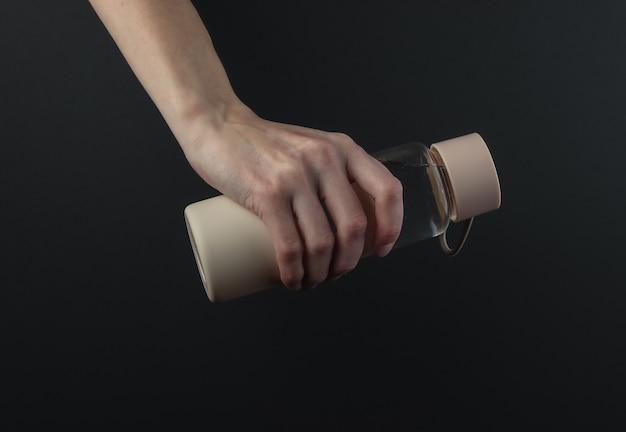 Main féminine tient une bouteille d'eau sur fond noir