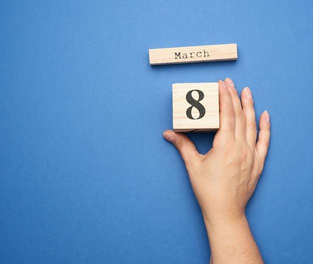 Main féminine tient le calendrier en bois avec la date du huit mars