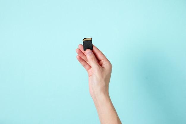 La main féminine tient la carte mémoire sd sur bleu. concept techno minimaliste.