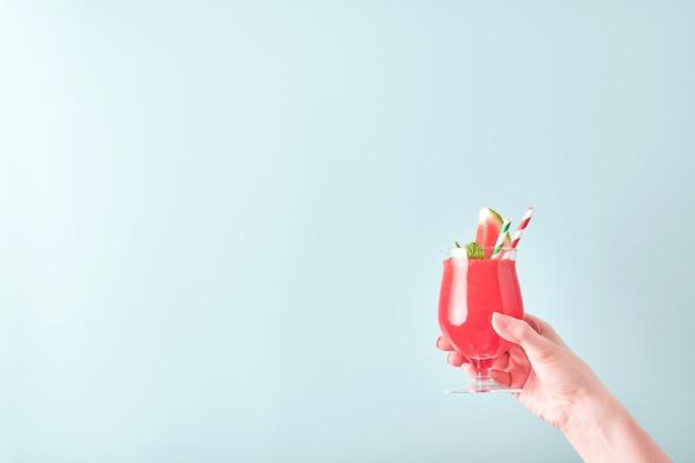 La main féminine tient un cocktail de pastèque en verre avec de la menthe et de la glace sur fond bleu. vacances d'été chaudes et colorées. fermez les tranches de pastèque dans les mains. bannière. maquette.