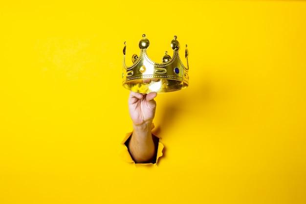 La main féminine tient une couronne d'or sur un fond jaune vif