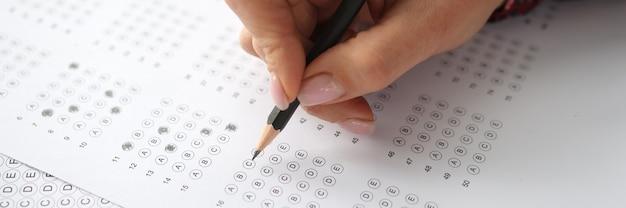 La main féminine tient un crayon et marque les réponses pour tester le concept de test d'embauche