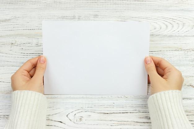 Une main féminine tient une enveloppe et une carte postale sur le bureau en bois