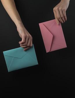 Main féminine tient des enveloppes sur fond noir