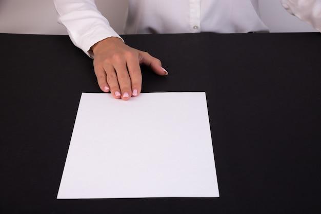 Une main féminine tient une feuille de papier vierge sur une table avec un fond noir