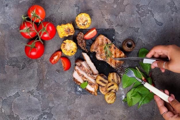 Une main féminine tient une fourchette avec un steak grillé sur une assiette en ardoise avec des épinards, des tomates et des pommes de terre grillées