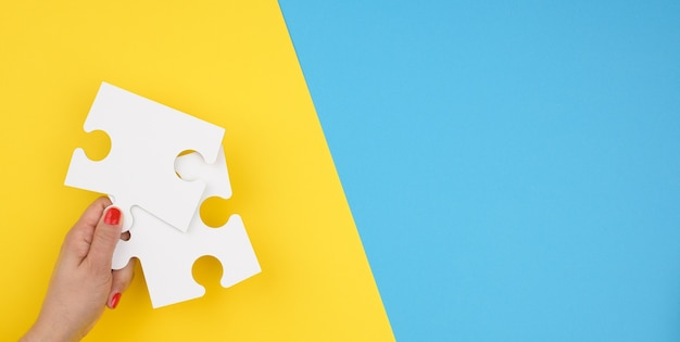 La main féminine tient un fragment d'un grand puzzle blanc sur fond bleu, le concept de trouver une idée, de résoudre un problème