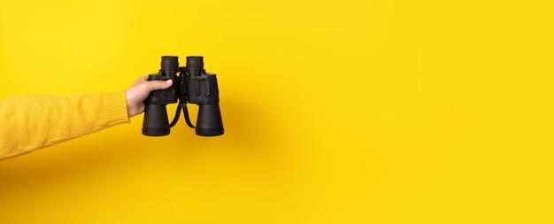 La main féminine tient des jumelles noires sur fond jaune. en regardant à travers des jumelles, voyagez, trouvez et recherchez le concept. bannière.