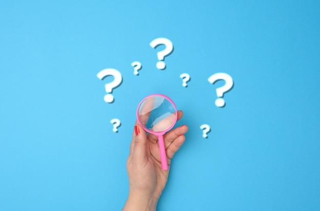 La main féminine tient une loupe en plastique et des points d'interrogation sur fond bleu. le concept de trouver une réponse aux questions, à la vérité et à l'incertitude.