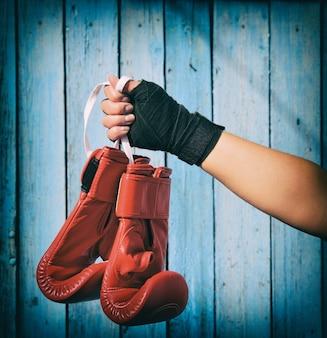 Une main féminine tient une paire de gants de kickboxing rouges