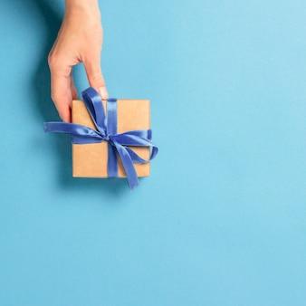 Une main féminine tient, prend, obtient un cadeau sur un fond bleu.