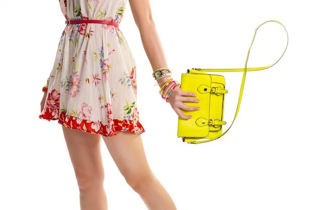 La main féminine tient le sac de citron vert. robe fleurie avec ceinture rouge. sac à main tendance acheté en boutique. bracelets colorés et montre classique.