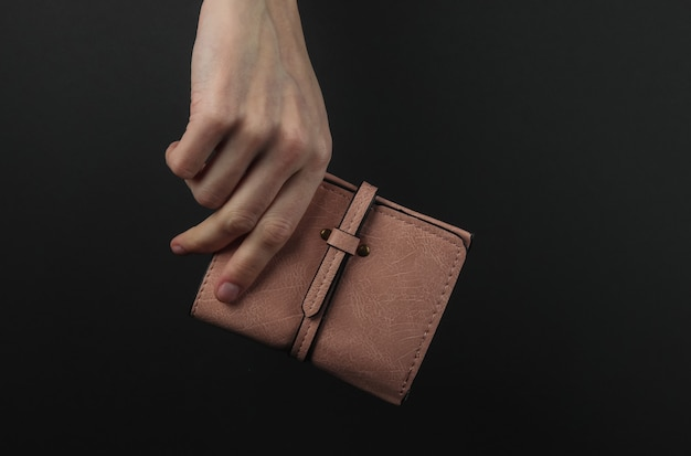 La main féminine tient un sac à main en cuir rouge sur fond noir