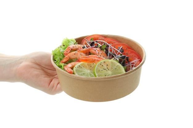 La main féminine tient la salade de crevettes, isolée sur fond blanc
