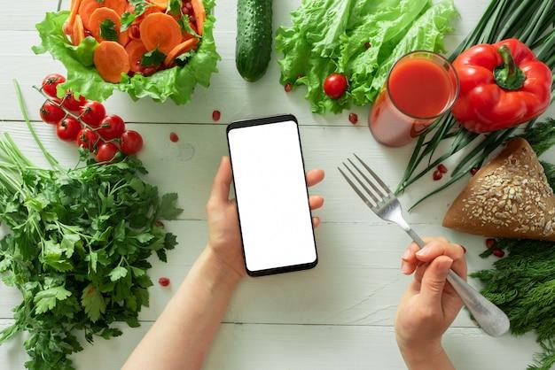 Main féminine tient un smartphone sur un fond de table avec des légumes de régime. place pour votre texte.