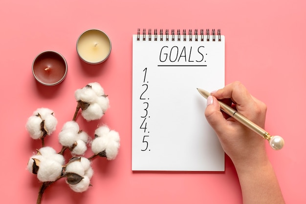La main féminine tient un stylo et écrit les objectifs du nouvel an 2021 sur le bloc-notes blanc