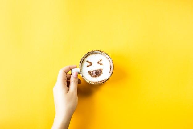 Une main féminine tient une tasse de café sur laquelle est tiré un rire emoji