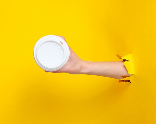 Une main féminine tient une tasse de café en papier à travers du papier jaune déchiré. concept minimaliste