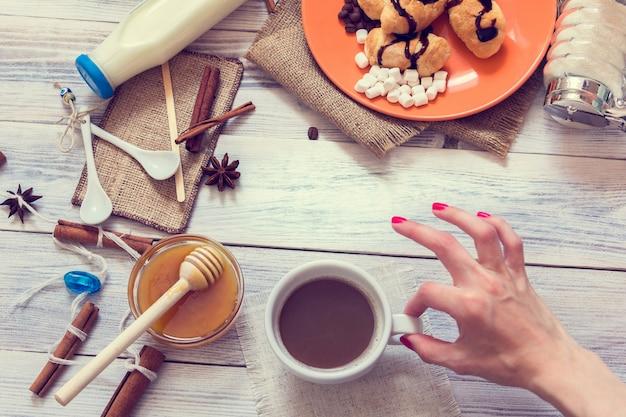 Une main féminine tient une tasse de café