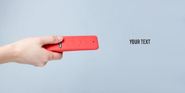 Main féminine tient la télécommande de la télévision moderne dans un boîtier en silicone rouge sur fond gris. copier l'espace