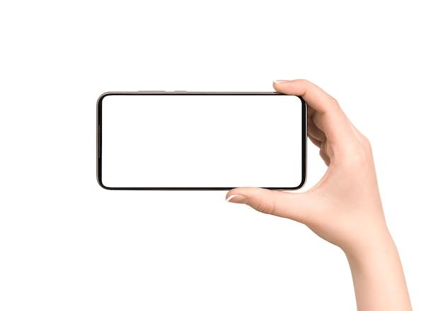 La main féminine tient un téléphone intelligent. vue de face sur un mur blanc isolé