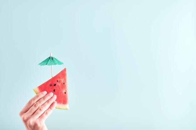 La main féminine tient une tranche de pastèque sur fond bleu. vacances d'été chaudes et colorées. fermez les tranches de pastèque dans les mains. bannière. maquette.