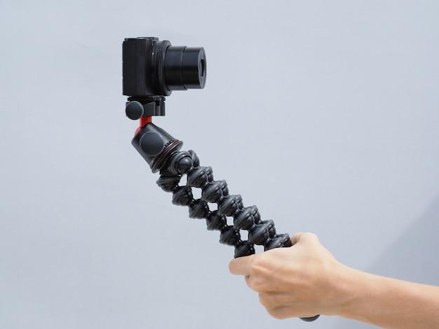 La main féminine tient un trépied avec un appareil photo numérique compact. concept de blogueur.