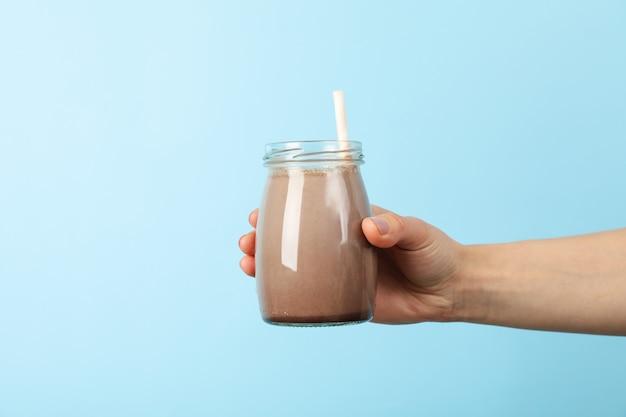 Main féminine tient un verre de lait frappé au chocolat sur bleu