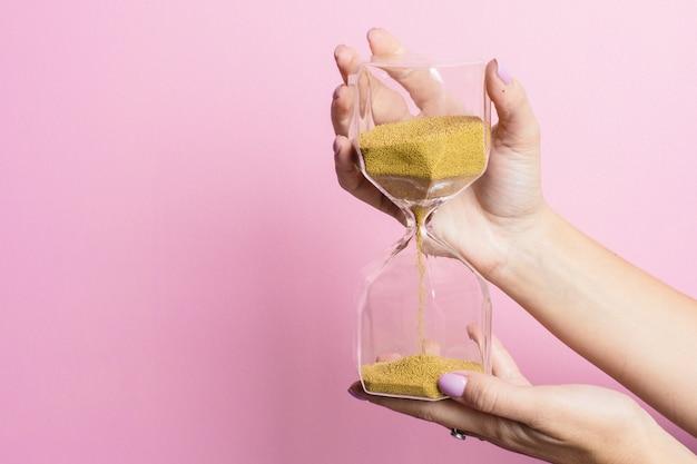 La main féminine tient un verre de sable sur une surface rose