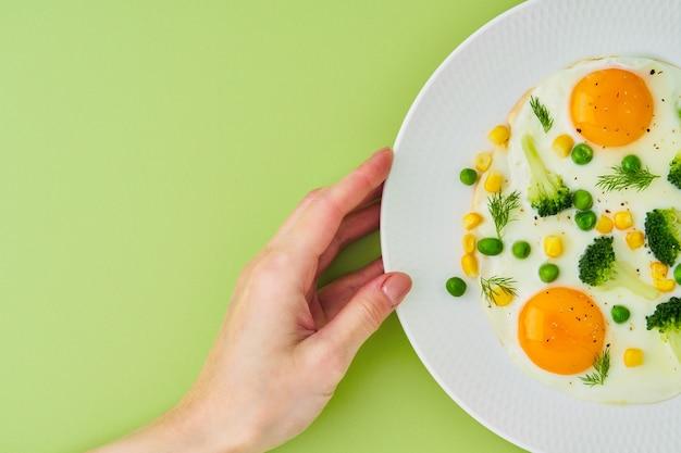 Main féminine touchant la plaque avec du maïs de brocoli d'oeufs frits sur le fond vert clair